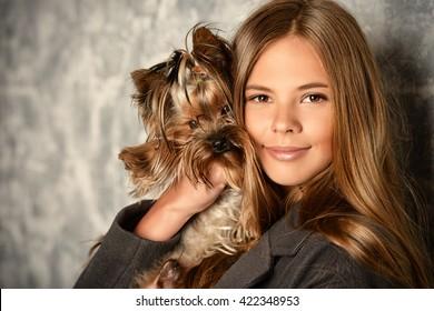 Happy girl holding her lovely yorkshire terrier dog.