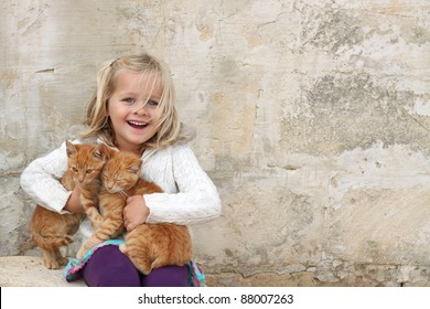 A happy girl holding a pair of cats. Space for free text