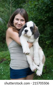 happy girl holding puppy St. Bernard