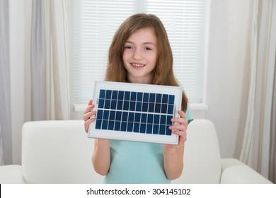 Happy Girl Holding Solar Panel In Living Room