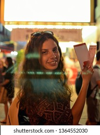 Happy girl holding tickets on Broadway