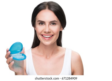 Happy girl holding transparent plastic teeth for orthodontic correction