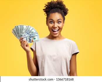 Happy girl holds cash money. Photo of african american girl wears casual outfit on yellow background. Emotions and pleasant feelings concept.