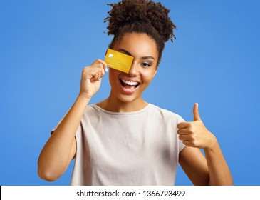 Happy girl holds credit card and shows thumb up. Photo of african american girl wears casual outfit on blue background. Emotions and pleasant feelings concept.