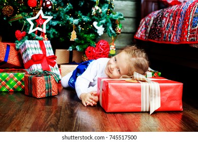 happy girl at home on the floor with Christmas tree and presents