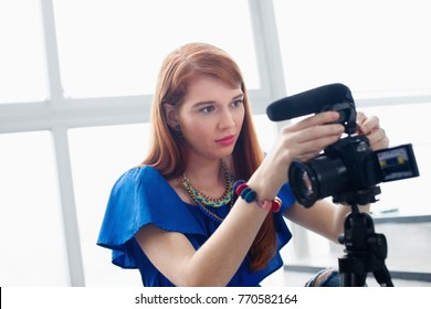 Happy girl at home setting video camera and attaching lens to dslr. People and technology, young woman working as vlogger. Web influencer recording message