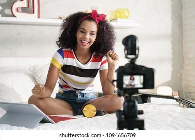 Happy Mädchen zu Hause sprechen vor der Kamera für vlog. Junge schwarze Frau, die als Bloggerin arbeitet und Video-Tutorial für das Internet aufnimmt