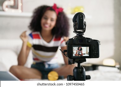Happy girl at home speaking in front of camera for vlog. Young black woman working as blogger, recording video tutorial for Internet