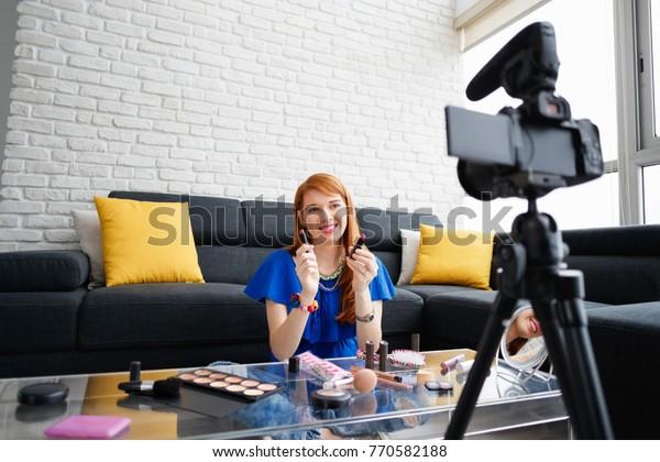 Chica feliz en casa hablando de maquillaje frente a la cámara. Gente y tecnología, mujer joven en el trabajo como vloguera. Mensaje de grabación con influencia web para redes sociales de internet