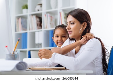 Happy girl hugging her mother who is working with documents at home
