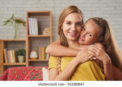 Happy girl hugging her mother from behind