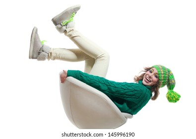 Happy girl in jeans, warm sweater, shoes with laces, bright green yellow knitted hat with big pompon, sitting on chair with legs up, looking at camera, laughing with toothy smile. Isolated on white