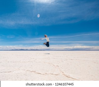 Happy girl in a jump in sunshine Salar de Uyuni in Bolivia