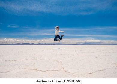 Happy girl in a jump in sunshine Salar de Uyuni in Bolivia