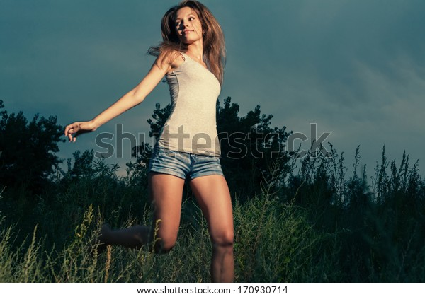 Happy girl jumping or dancing in a high grass