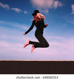 Happy girl jumping on the roof in sunny day