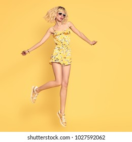 Happy girl Jumping in Studio on Yellow background. Blond Slim Model Having Fun in Fashionable Sunglasses, Trendy Summer Playsuit. Young Playful Beautiful woman in Stylish Outfit