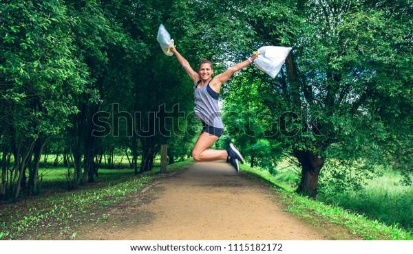Happy Girl Springen mit Mülltüten nach dem Holzeinschlag