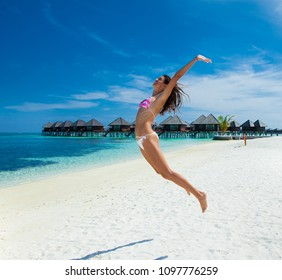 Happy girl jumps at topical beach on Olhuveli island in Maldives.