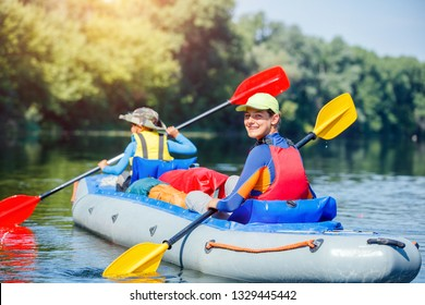 Happy girl kayaking on the river. Active girl with her brother having fun and enjoying adventurous experience with kayak on a sunny day during summer vacation