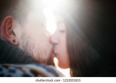 Happy girl kiss boyfriend with a red beard against sunshine. Happy moments. Close up defocused portrait