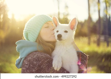 Happy girl kissing her dog - a small white Swiss Shepherd puppy