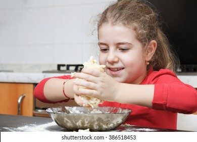 happy girl kneading dough with hands in the kitchen