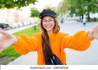 Happy girl in knitted  orange sweater  making self portrait  in park early in evening.  Trendy cap, round glasses.
