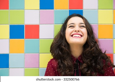 Happy girl laughing against a colorful tiles background. Concept of joy