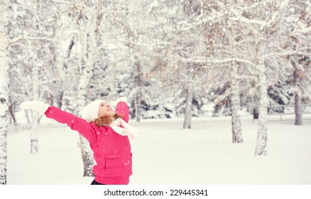 happy girl laughing, enjoying life and throws snow at winter outdoors