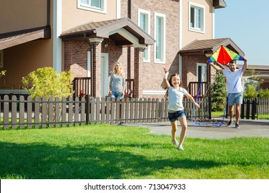 Happy girl launching kite together with father