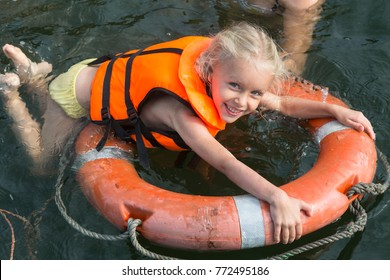 Happy girl with lifebuoy and life jacket enjoying in sea.