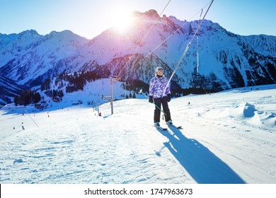Happy girl lifting on the ski drag lift rope in bright sport outfit over sunset light near mountain peak