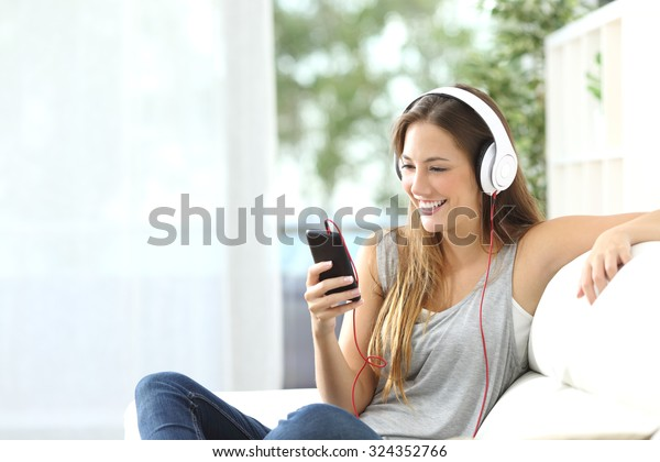 Fröhliches Mädchen, das Musik vom Handy hört, sitzend auf einem Sofa zu Hause