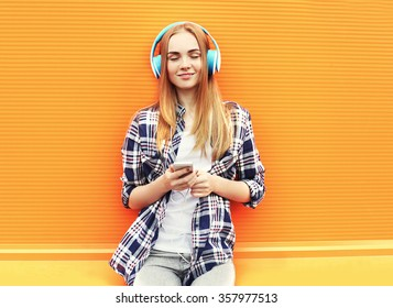 Happy girl listens and enjoys good music in headphones over colorful orange background
