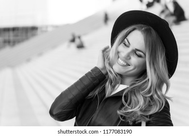 Happy girl with long blond hair, hairstyle, in paris, france. Girl in black hat smile outdoor, fashion. Beauty, look, makeup. Fashion, style accessory Youth skincare visage