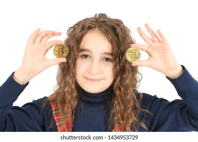 Happy girl with long curly hair holds a gold bitcoin in her hand. High resolution photo. Full depth of field.