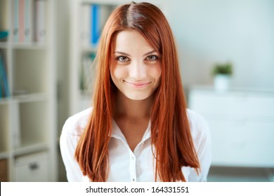 Happy girl with long ginger hair looking at camera