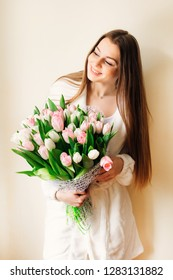 Happy girl with long hair and big bouquet of white and pink tulips.