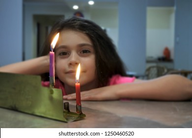 Happy girl looking at the first candles of Chanukah Jewish Holiday on a Chanukiah