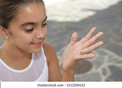 Happy girl looking at a grasshopper that is on her hand