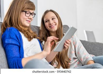 Happy girl looking at sister using digital tablet on sofa at home