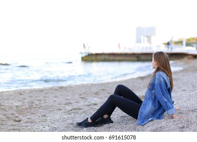 Happy girl looks at camera with beautiful and sweet smile, enjoying pleasant pastime and driving hands over warm sand with seashells, sitting on beach and looking toward endless blue sea on pleasant
