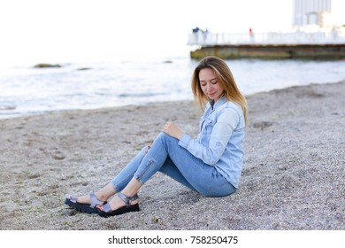 Happy girl looks at camera with beautiful and sweet smile, enjoying pleasant pastime, sitting on beach and looking toward endless blue sea on pleasant evening. Young European-looking woman with blond
