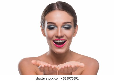 Happy girl looks at her hands with a place for inserting the tube of a cream with an opened mouth and sincere smile. Bright professional make-up: wet silver eyeshadows and intensive pink lipstick.