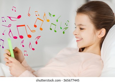 happy girl lying in bed with smartphone over notes