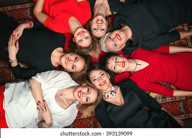 Happy girl lying in a circle. Beautiful girlfriend lie on the floor, the red carpet and laugh merrily. Girls lying on the back. Female group, people, smiling, womens, fun, cheerful, hen-party