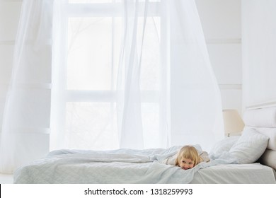 Happy girl lying down on bed in cozy white room with window on background