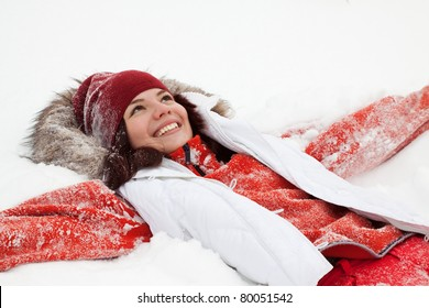 Happy girl lying down on the snow in winter