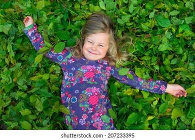 happy girl is lying in green leaves